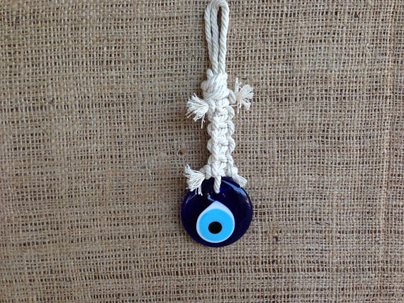 evil eye wall hanging on dirty white cord